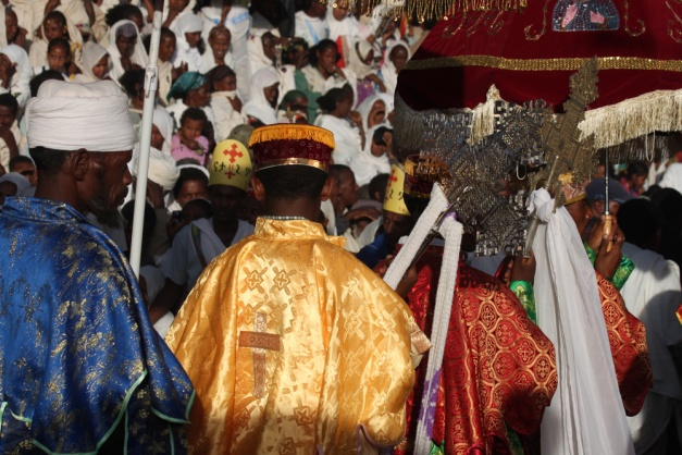Colourful robed priest with processional crosses, ETHIOPIA