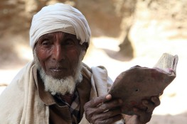 Pilgrim with old bound bible, Lalibela