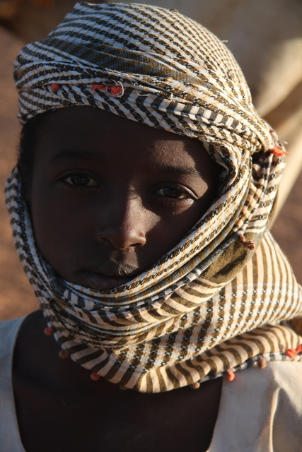 Young Sudanese boy in traditional khaffiyeh scarf, Meroe